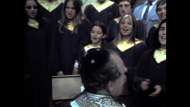 vídeos y material grabado en eventos de stock de panning shot of girls in the choir singing; all dressed in black and golden uniform and crowd of people in the background - torah
