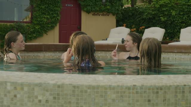 panning shot of girls relaxing in backyard swimming pool / cedar hills, utah, united states - utebassäng bildbanksvideor och videomaterial från bakom kulisserna