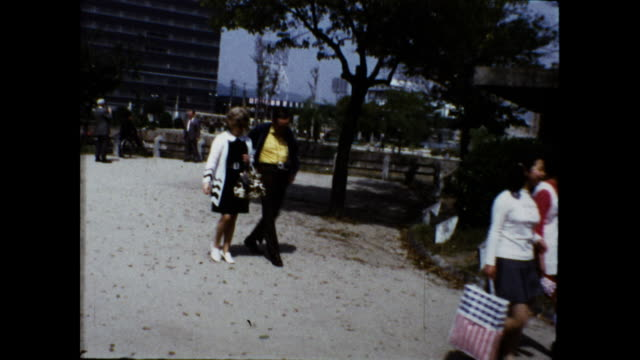 vidéos et rushes de panning shot of group of people walking on the street, man in green cardigan wearing a camera around his neck; fountain and tall building in the... - cardigan