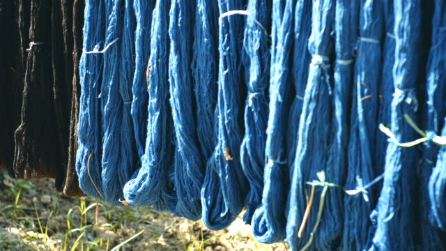 panning shot of hanged dyed raw fabric - navy blue stock videos & royalty-free footage
