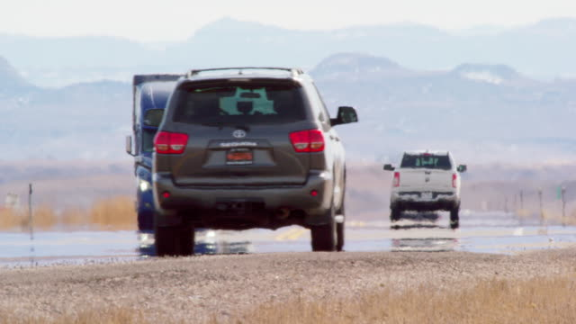 panning shot of heat haze distorting video of semi-trucks and other vehicles driving down a utah interstate surrounded by mountains on a sunny day - sports utility vehicle stock videos & royalty-free footage