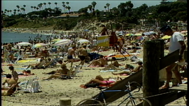 panning shot of heavily crowded beach - anno 1987 video stock e b–roll