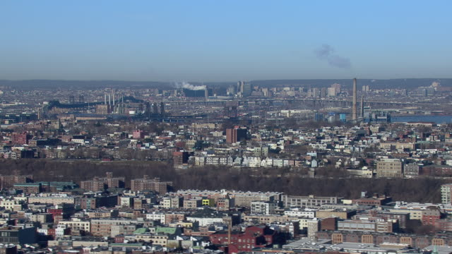 Panning shot of Hoboken and Jersey City, New Jersey, with the cities of Kearny and Newark visible in the distance.