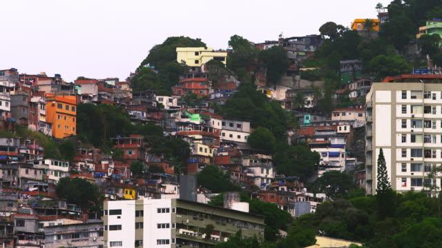 Panning shot of houses at a favela along the mountainside in Rio de Janeiro, Brazil