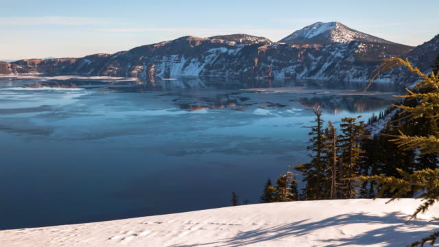 panning shot of ice floating on crater lake near mountains and snow against sky from day - オレゴン州クレーター湖点の映像素材/bロール
