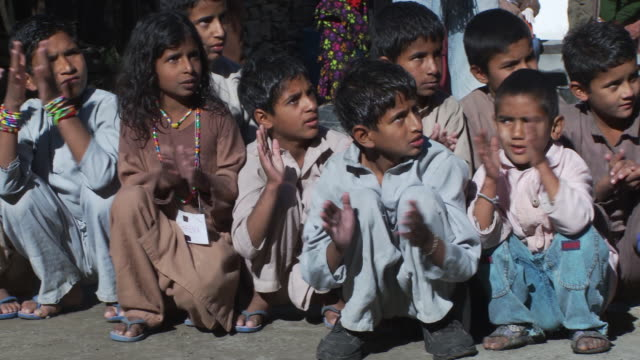 panning shot of little children clapping - orphan stock videos and b-roll footage