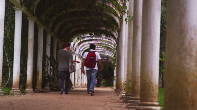 stockvideo's en b-roll-footage met panning shot of male and female walking under arches. - tuinpad