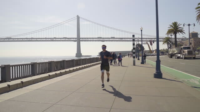 panning shot of male sportsperson jogging on bridge during sunny day - san francisco, california - san francisco oakland bay bridge stock videos & royalty-free footage