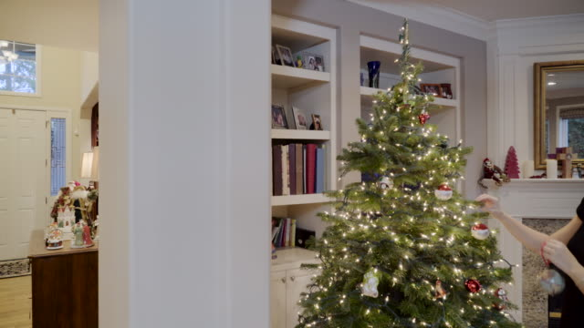 vidéos et rushes de panning shot of man and woman decorating tree - panoramique