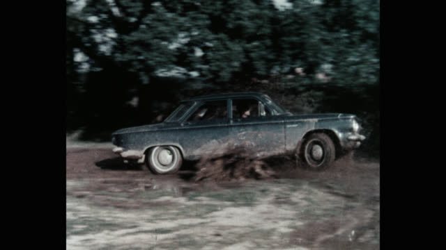 panning shot of man driving car through mud on dirt road - dirt track stock videos & royalty-free footage