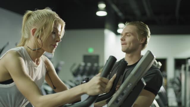 panning shot of man flirting with irritated woman riding stationary bike in gymnasium / american fork, utah, united states - flirtare video stock e b–roll