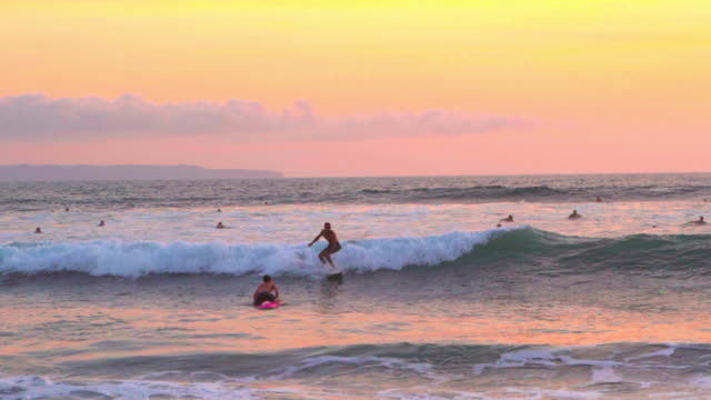 panning shot of man surfing on wave amidst people in sea against sky during sunset - canggu, bali - bali stock videos & royalty-free footage