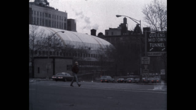 1979 panning shot of man walking on street near queens–midtown tunnel, new york city, new york state, usa - arrow symbol stock videos & royalty-free footage
