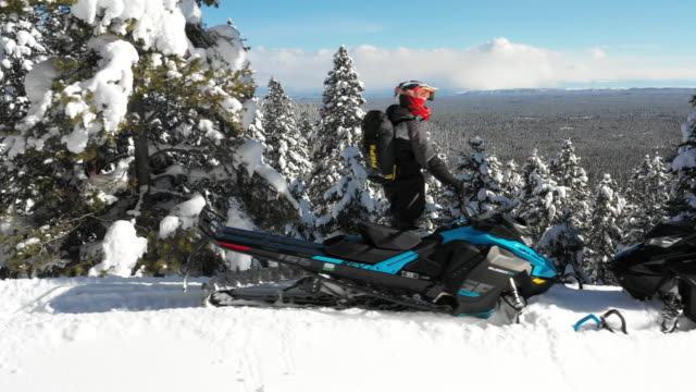 Panning shot of men with snowmobiles admiring scenic view from mountain / Island Park, Idaho, United States
