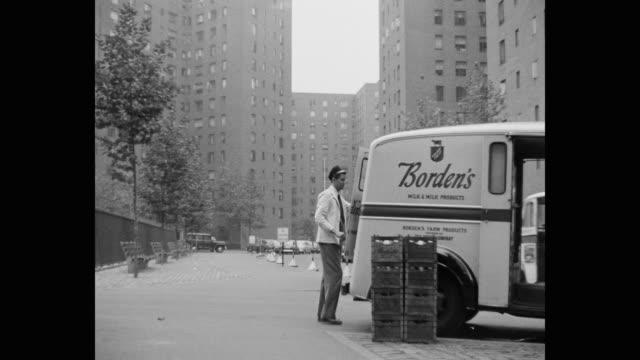 vídeos y material grabado en eventos de stock de 1952 panning shot of milkman delivering milk in stuyvesant town–peter cooper village, nyc, new york, usa - leche
