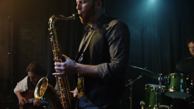 Panning shot of musician playing saxophone / Provo, Utah, United States,