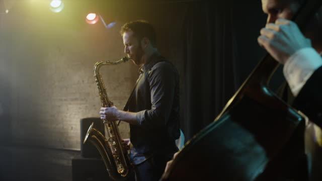 panning shot of musicians playing musical instruments / provo, utah, united states,  - ジャズ点の映像素材/bロール