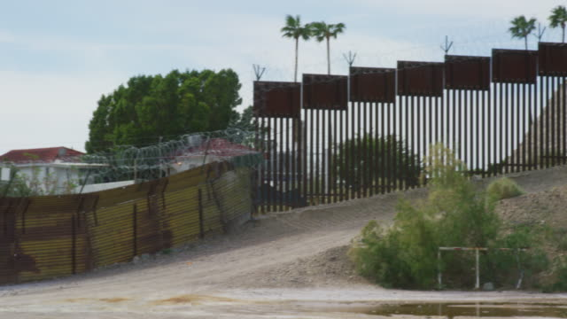 vidéos et rushes de panning shot of parts of the old and new steel-slat border wall topped by razor wire (on the us side) between mexico and the united states with the town of los algodones and palm trees on the other side and bushes in the foreground - clôture