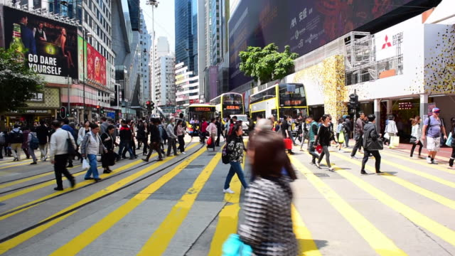 panning shot of people crossing street amidst buildings and vehicles in city on sunny day - hong kong, china - hong kong stock videos & royalty-free footage
