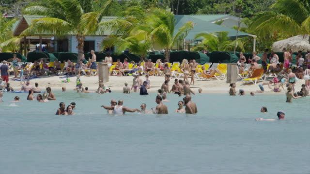 Panning shot of people enjoying the beach and ocean / Roatan, Honduras, Central America,