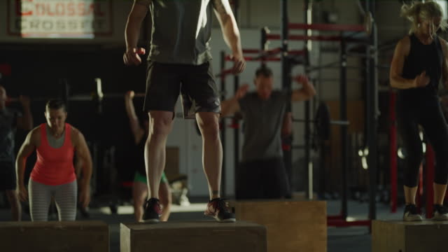 Panning shot of people jumping on boxes in cross training gymnasium / Lehi, Utah, United States