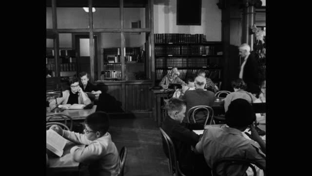 vídeos de stock e filmes b-roll de 1956 panning shot of people reading books in public library - imagem em movimento