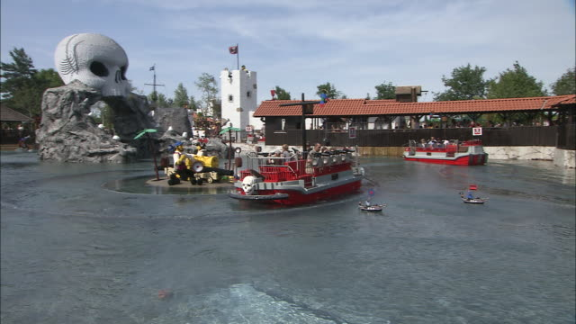 Panning shot of people riding ships in a lagoon with water cannons
