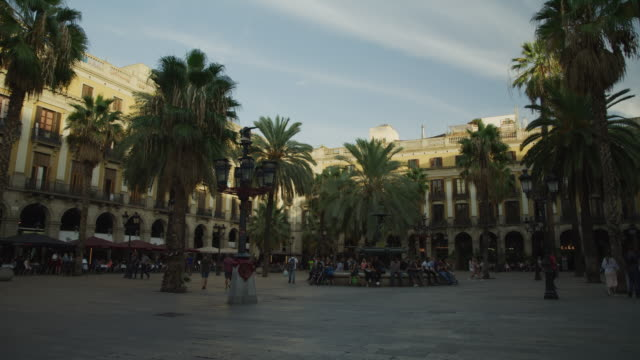 vidéos et rushes de panning shot of people walking in urban plaza / barcelona, barcelona, spain - barcelone