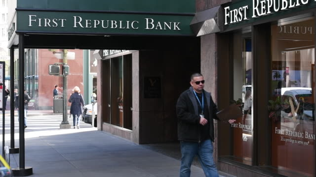 Panning shot of person walking into First Republic Bank to the bank's sign in San Francisco California on Friday March 31 2017
