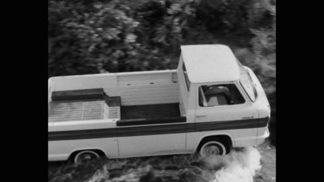 panning shot of pick-up truck driving in stream passing through forest - シボレー点の映像素材/bロール