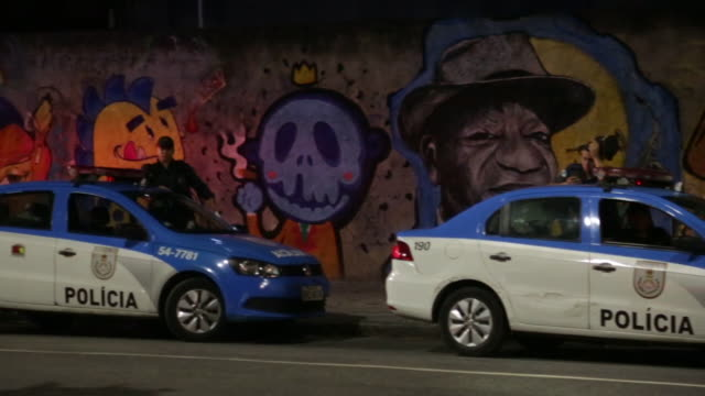 panning shot of police cars parked in front of street art in rio de janeiro - police car stock videos and b-roll footage
