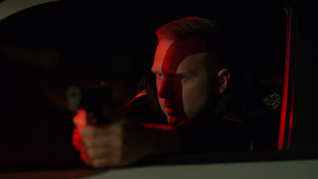 vídeos y material grabado en eventos de stock de panning shot of policeman leaning on car door aiming gun at night / eagle mountain, utah, united states - apuntar