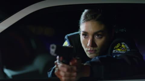 vidéos et rushes de panning shot of policewoman leaning on car door aiming gun at night / eagle mountain, utah, united states - police