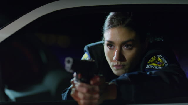 panning shot of policewoman leaning on car door aiming gun at night / eagle mountain, utah, united states - police force stock videos and b-roll footage