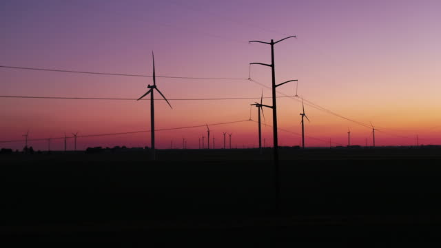 Panning shot of power line and wind turbine silhouettes at sunset