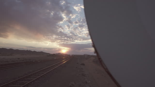 panning shot of railroad track on land against sky during sunset - swakopmund, namibia - railway track stock videos & royalty-free footage