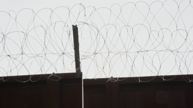 panning shot of razor wire across the top of the border wall between mexico and the united states (shot from the us side) on a partly cloudy day before settling on the sky - barbed wire stock videos & royalty-free footage