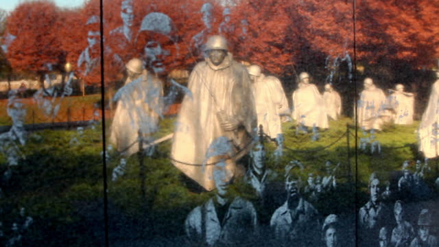 Panning shot of reflection of statues on the Korean War Veterans Memorial wall in Washington DC