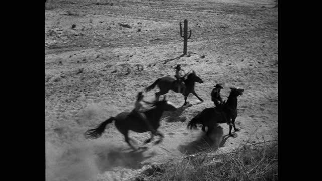 vídeos de stock e filmes b-roll de panning shot of renegades firing guns while riding horses in desert - bandido