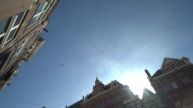 panning shot of residential buildings against sky on sunny day - a forma di croce video stock e b–roll
