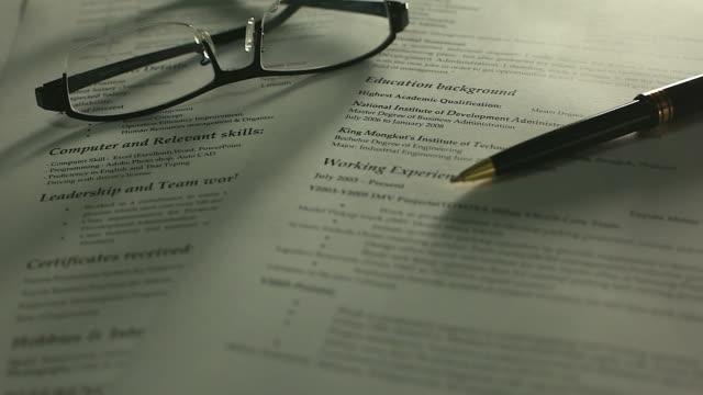 ペン、メガネで作業机の上履歴書を流し撮り。