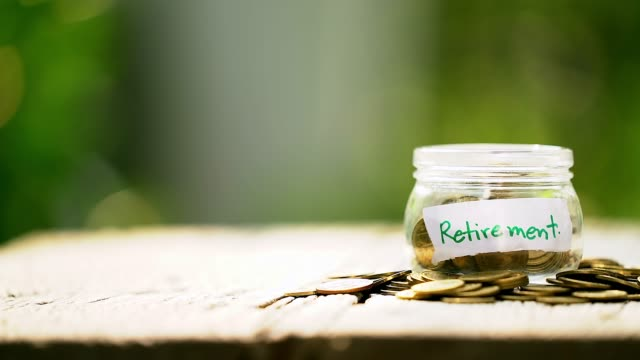 panning shot of retirement word with coin in glass jar, savings and financial investment concept. - jar stock videos & royalty-free footage