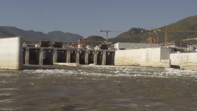 panning shot of river flowing from dam with cranes near mountain against sky on sunny day - luang prabang, laos - dam stock videos & royalty-free footage