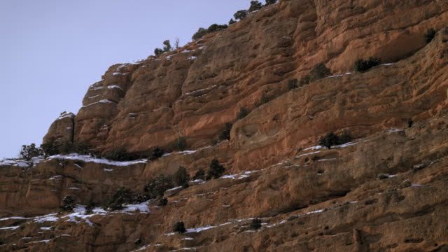 panning shot of rocky cliffs with snow. - プロボ点の映像素材/bロール