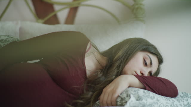 panning shot of sad pregnant girl falling asleep on sofa / cedar hills, utah, united states - sdraiato video stock e b–roll