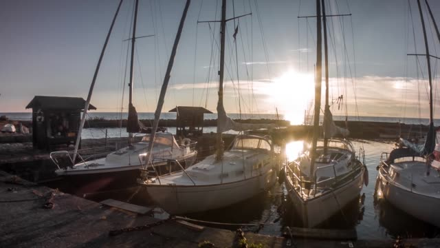 stockvideo's en b-roll-footage met panning shot van zeilboten in een haven in denemarken bij zonsondergang - aangelegd