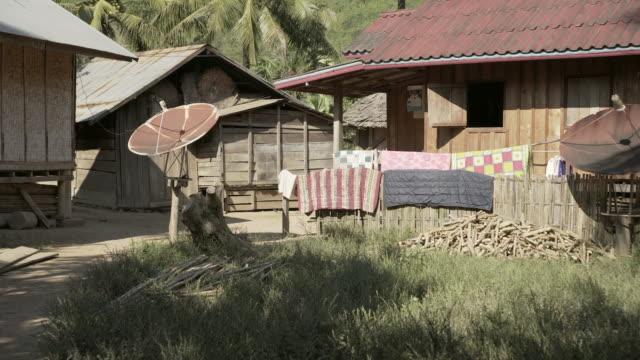 vídeos de stock, filmes e b-roll de panning shot of satellite dish by plants growing in backyard of house on sunny day - chiang rai, thailand - equipamento de telecomunicações