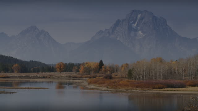 panning shot of scenic view of mountain range near river bend in autumn / grand teton national park, wyoming, united states - grand teton national park stock videos & royalty-free footage