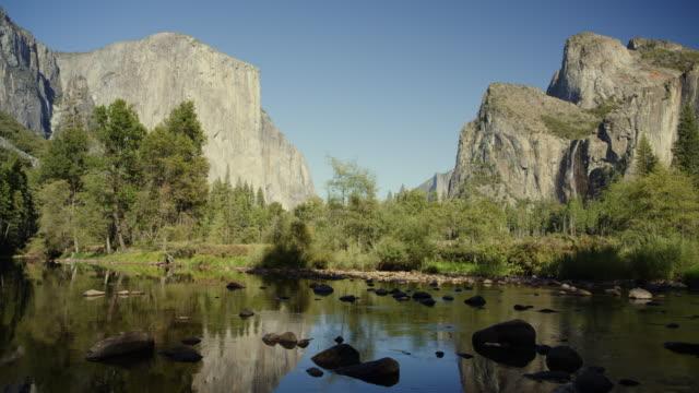panning shot of scenic view of river near trees and el capitan / yosemite valley, california, united states - エルキャピタン点の映像素材/bロール