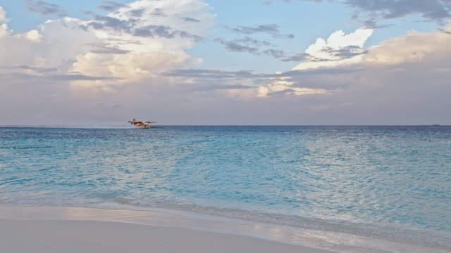 Panning shot of seaplane taking off from the tropical sea of Maldives